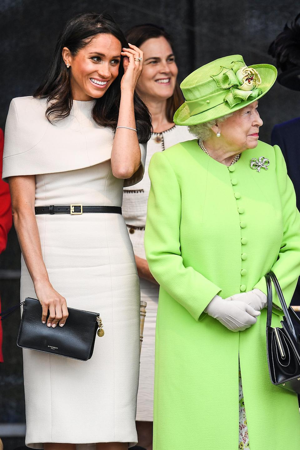 <p>Meghan wore a custom oat-coloured Givenchy dress with a cape for her joint engagement with the Queen in Chester in June 2018. According to Elle, it's believed to have cost £13,704 [Photo: Getty] </p>