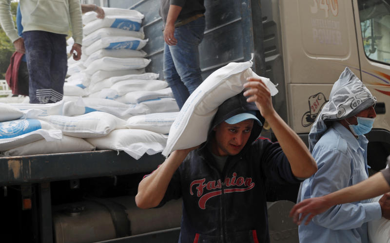 Palestinian workers unloads sacks of flour distributed by the United Nations Relief and Works Agency (UNRWA) for poor refugee families, at the Sheikh Redwan neighborhood of Gaza City, Tuesday, March 31, 2020. The United Nations has resumed food deliveries to thousands of impoverished families in the Gaza Strip after a three-week delay caused by fears of the coronavirus. UNRWA, provides staples like flour, rice, oil and canned foods to roughly half of Gaza's 2 million people. (AP Photo/Adel Hana)