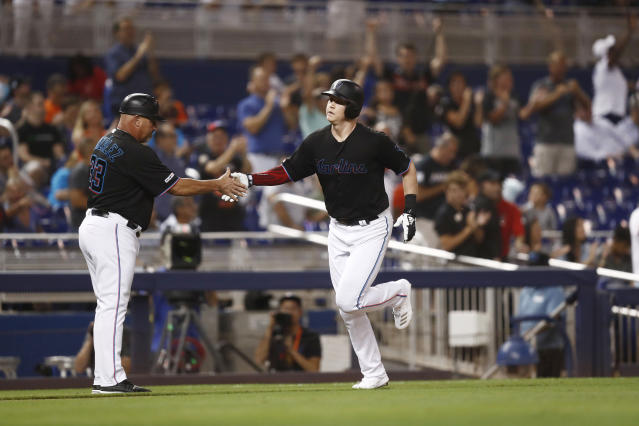 Miami Marlins' Garrett Cooper, right, is greeted by third base coach Fredi Gonzalez (33) after hitting a home run during the third inning of the team's baseball game against the Miami Marlins on Friday, July 12, 2019, in Miami. (AP Photo/Brynn Anderson)