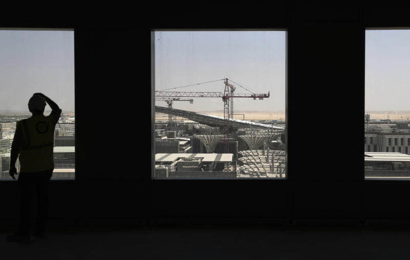 In this Oct. 8, 2019, photo, a visitor looks at the Sustainability Pavilion of the under construction site of the Expo 2020 in Dubai, United Arab Emirates. Dubai is betting billions of dollars that its Expo 2020 will draw 25 million visitors, encourage business and spur development of the city. (AP Photo/Kamran Jebreili)