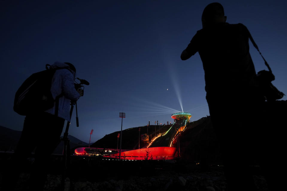 Journalists film a light show at the National Ski Jumping Centre, one of the venues for Beijing 2022 Olympic and Paralympic Winter Games, during a media tour in Zhangjiakou in northwestern China's Hebei province on Wednesday, July 14, 2021. (AP Photo/Andy Wong)