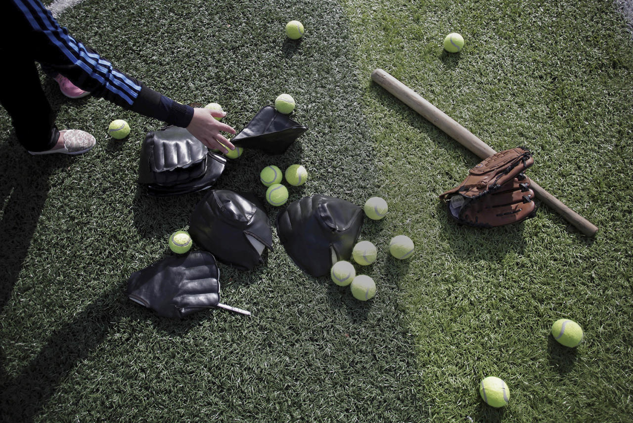 <p>A Palestinian woman chooses equipment before starting to train for an all-women's baseball game on a soccer field in Khan Younis, southern Gaza Strip, March 19, 2017. The female players wear hijabs, not helmets; toss around tennis balls, not baseballs; and their leather gloves have been replaced with black imitations knitted from fabric. The young women are trying to bring women's baseball to Gaza — giving the traditional American pastime a distinctly local feel. (Khalil Hamra/AP) </p>