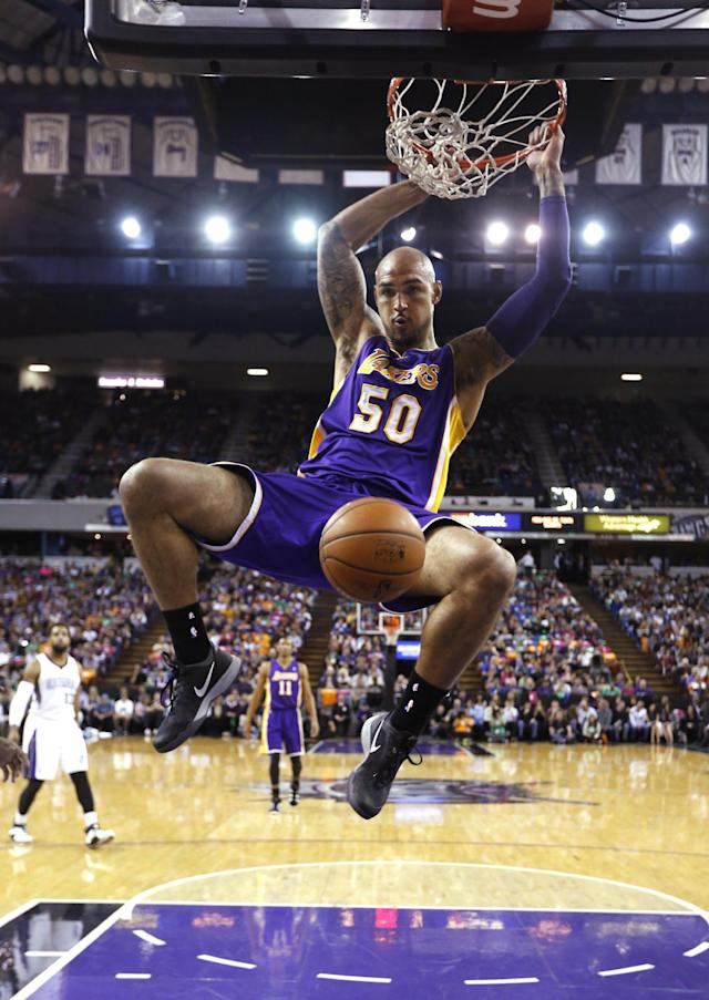 Los Angeles Lakers center Robert Sacre hangs on the rim after a dunk against the Sacramento Kings during the first quarter of an NBA basketball game Wednesday, April 2, 2014, in Sacramento, Calif.( AP Photo/Rich Pedroncelli)