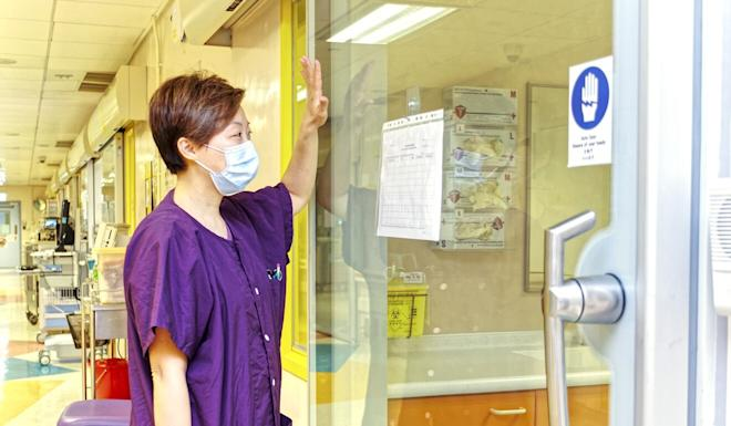 Chan Ying-fei communicates with a child patient through the glass of an isolation ward. Photo: Handout