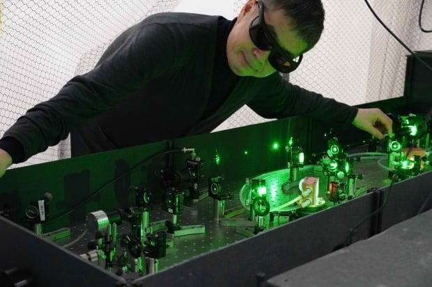 Chemistry professor Takamasa Momose, a member of the ALPHA collaboration, poses with his laser system at the University of British Columbia. The main components of the system,  used to manipulate antimatter atoms, were designed and built by Momose and students in his lab.                  (Takamasa Momose - image credit)