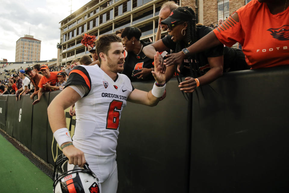 FILE - In this Oct. 27, 2018, file photo, Oregon State quarterback Jake Luton high fives fans after the team's overtime win against Colorado in an NCAA football game, in Boulder, Colo. Jake Luton is determined to make the most of his last chance. After a career marred by injury, he was granted a sixth season of eligibility. (AP Photo/Jack Dempsey, File)