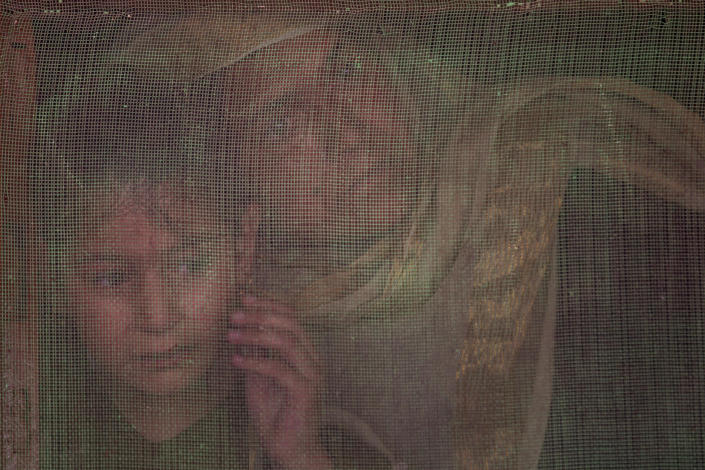 A Kashmiri woman and a child watch from behind a window mesh the funeral of Waseem Ahmed, a policeman who was killed in a shootout, on the outskirts of Srinagar, Indian controlled Kashmir, Sunday, June 13, 2021. Two civilians and two police officials were killed in an armed clash in Indian-controlled Kashmir on Saturday, police said, triggering anti-India protests who accused the police of targeting the civilians. (AP Photo/Dar Yasin)