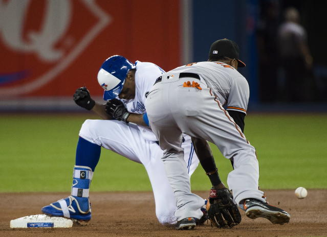 Toronto Blue Jays' Curtis Granderson (18) slides safely into second base past Baltimore Orioles shortstop Tim Beckham (1) after Granderson hit a double during the first inning of a baseball game, Tuesday, Aug. 21, 2018, in Toronto. (Nathan Denette/The Canadian Press via AP)