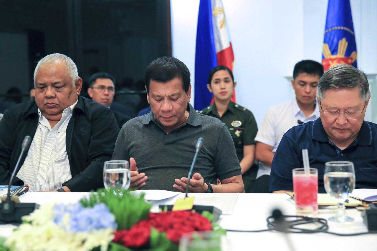 In this photo provided by the Presidential Communications Operations Office, Philippine President Rodrigo Duterte, center, prays beside Executive Secretary Salvador Medialdea, left, and Finance Secretary Carlos Dominguez, right, before the start of a special cabinet meeting in Davao city, Mindanao, southern Philippines, Thursday, May 25, 2017. Duterte declared 60 days of martial law on Tuesday across the southern third of the nation, an area that includes Marawi but extends well beyond it. ISIS-linked militants launched a violent siege in Marawi that sent thousands of people fleeing for their lives and raised fears of extremists gaining traction in the country. (Presidential Communications Operations Office via AP)