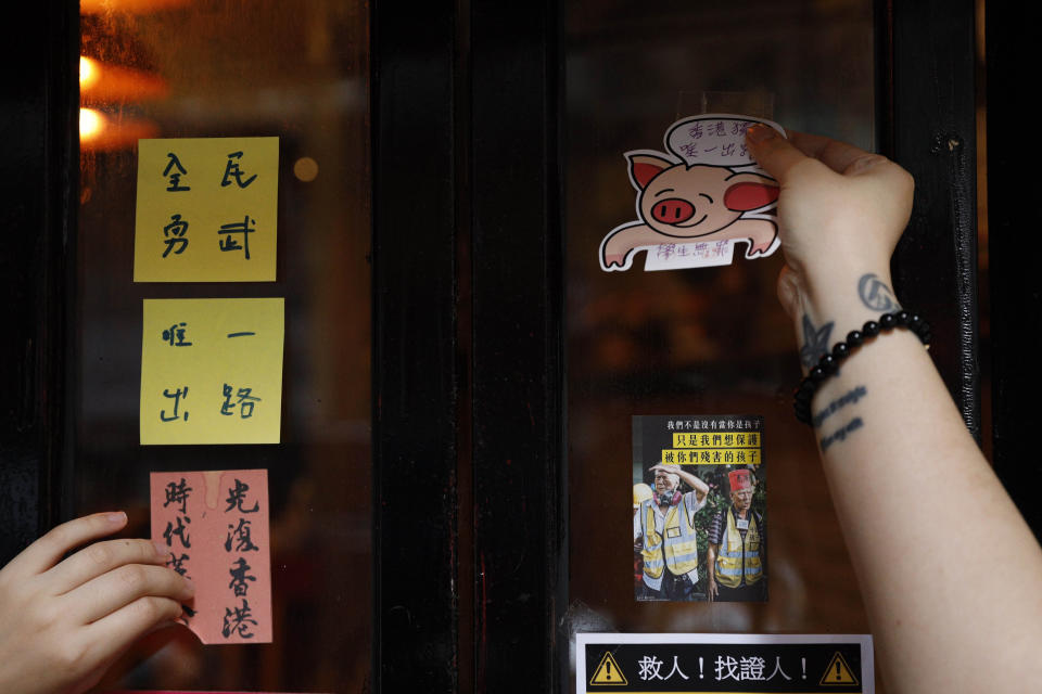 An employee removes stickers and posters with messages in support of the pro-democracy movement at a restaurant in Hong Kong, Thursday, July 2, 2020. Hong Kong police have made the first arrests under a new national security law imposed by mainland China, as thousands of people defied tear gas and pepper pellets to protest against it. Police say they arrested 10 people under the law, including at least one who was carrying a Hong Kong independence flag. (AP Photo/Kin Cheung)