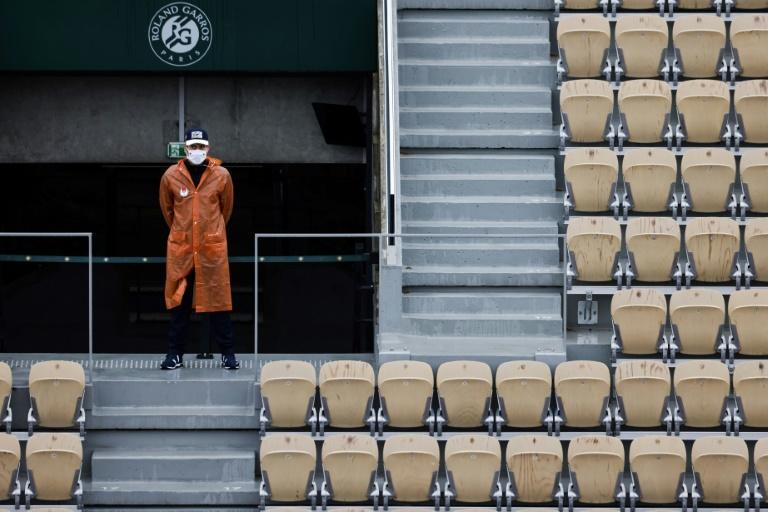 A member groundstaff stands among the empty seats on the opening day of Roland Garros