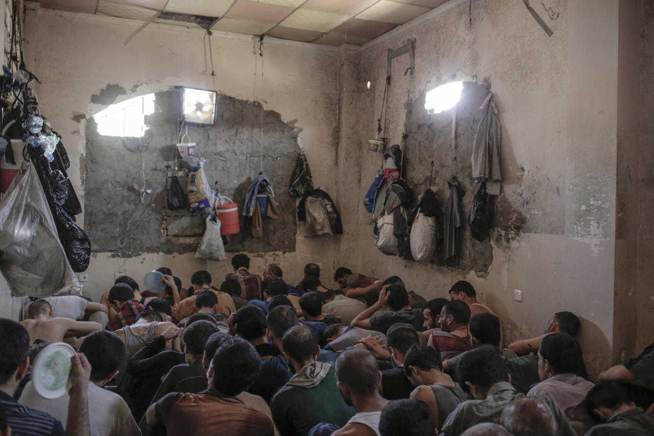 FILE -In this Tuesday, July 18, 2017 file photo, suspected Islamic State members sit inside a small room in a prison south of Mosul. A French woman captured in Mosul with her four small children is facing possible prosecution in Iraq for collaborating with the Islamic State group, in a test case for how governments handle families of foreign fighters now that the extremists are in retreat. (AP Photo/Bram Janssen, File)