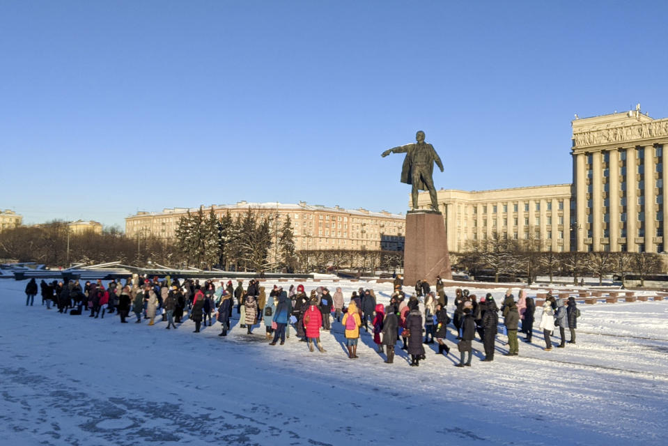 """People gather for a flashmob in support of Russian President Vladimir Putin at a Vladimir Lenin in St. Petersburg, Russia, Monday, Feb. 8, 2021. Kremlin-backed media reported that a grassroots flashmob titled """"Putin is our president"""" started sweeping the country. State news channel Rossiya 24 aired videos from different cities of people dancing to patriotic songs and waving Russian flags, describing them as a genuine expression of support for Putin. (AP Photo)"""