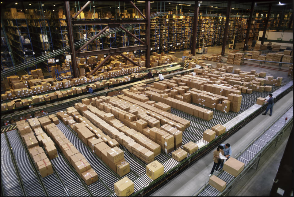 Overview of a large industrial distribution warehouse storing products in cardboard boxes on conveyor belts and racks.