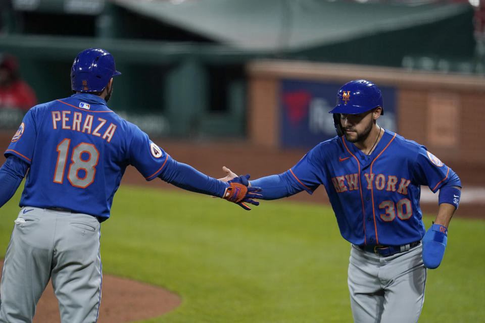 New York Mets' Michael Conforto (30) is congratulated by teammate Jose Peraza after scoring during the fifth inning in the second game of a baseball doubleheader against the St. Louis Cardinals Wednesday, May 5, 2021, in St. Louis. (AP Photo/Jeff Roberson)