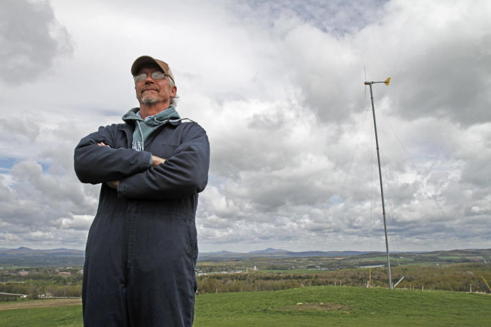 Bryan Davis stands on the hilltop with his wind turbine on Friday, May 11, 2012 in Derby Line, Vt. A Vermont wind power developer and two dairy farmers in the border community of Derby Line say they've been surprised at the level of opposition to a plan to build two turbines that has been coming from the Quebec town of Stanstead.(AP Photo/Toby Talbot)