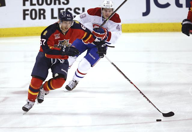 Montreal Canadiens' Michael Bournival (49 chases Florida Panthers' Vincent Trocheck (67) trying to steal the puck during the first period of an NHL hockey game in Sunrise, Fla., Saturday, March 29, 2014. (AP Photo/J Pat Carter)