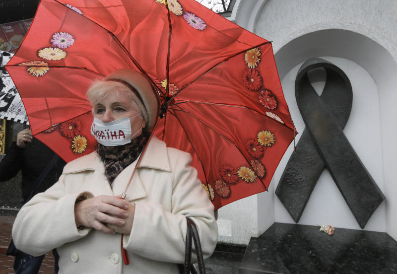 FILE - In this Tuesday, Nov. 13, 2012 file photo, a Ukrainian woman wearing a medical mask demonstrates in front of the memorial monument to AIDS victims in Kiev, Ukraine. An estimated 230,000 Ukrainians, or about 0.8 percent of people aged 15 to 49 in a population of 46 million, are living with HIV, the virus that causes AIDS. Some 120,000 are in urgent need of anti-retroviral therapy, which can greatly prolong and improve the quality of their lives. But due to a lack of funds, less than a quarter are receiving the drugs, one of the lowest levels in the world. (AP Photo/Efrem Lukatsky)