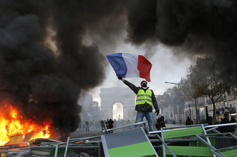 <p> A demonstrator waves the French flag onto a burning barricade on the Champs-Elysees avenue with the Arc de Triomphe in background, during a demonstration against the rising of the fuel taxes, Saturday, Nov. 24, 2018 in Paris. French police fired tear gas and water cannons to disperse demonstrators in Paris Saturday, as thousands gathered in the capital and staged road blockades across the nation to vent anger against rising fuel taxes and Emmanuel Macron's presidency.(AP Photo/Michel Euler) </p>