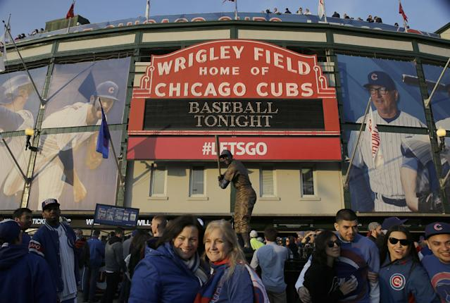 Fans gather outside of Wrigley Field before a Major League Baseball season-opening game between the Chicago Cubs and the St. Louis Cardinals in Chicago, Sunday, April 5, 2015. (AP Photo/Nam Y. Huh)