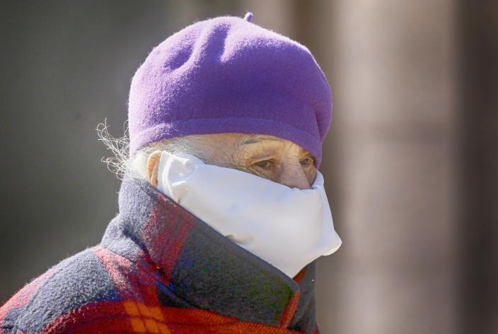 An elderly woman wearing a hand made face mask to help protect herself from the coronavirus walks in center Kyiv, Ukraine, Friday, March 26, 2021. Ukraine, which is struggling with a third wave of rising coronavirus infections, has recorded its highest daily death toll from COVID-19. Ukraine began vaccinations only in late February after receiving 500,000 doses of the AstraZeneca vaccine, but reluctance to take the shots is strong even as new infections severely tax the country's underfunded medical system. (AP Photo/Efrem Lukatsky)