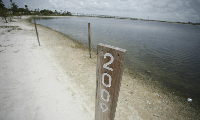 """In this June 27, 2011 photo, three wooden markers show where the shore line was in three past droughts at Clear Lake in West Palm Beach, Fla. This years' drought has taken more of a toll on the lake than the ones in 2001, 2007 and 2009. The lake houses some of the city's drinking water. South Florida's drought problem has reached a critical stage. The National Weather Service rates parts of South Florida at drought stage, D4, or the """"exceptional drought"""" stage. (AP Photo/J Pat Carter)"""