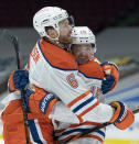Edmonton Oilers' Adam Larsson (6) and Josh Archibald (15) celebrate a goal against the Vancouver Canucks during the third period of an NHL hockey game Tuesday, Feb. 23, 2021, in Vancouver, British Columbia. (Jonathan Hayward/The Canadian Press via AP)
