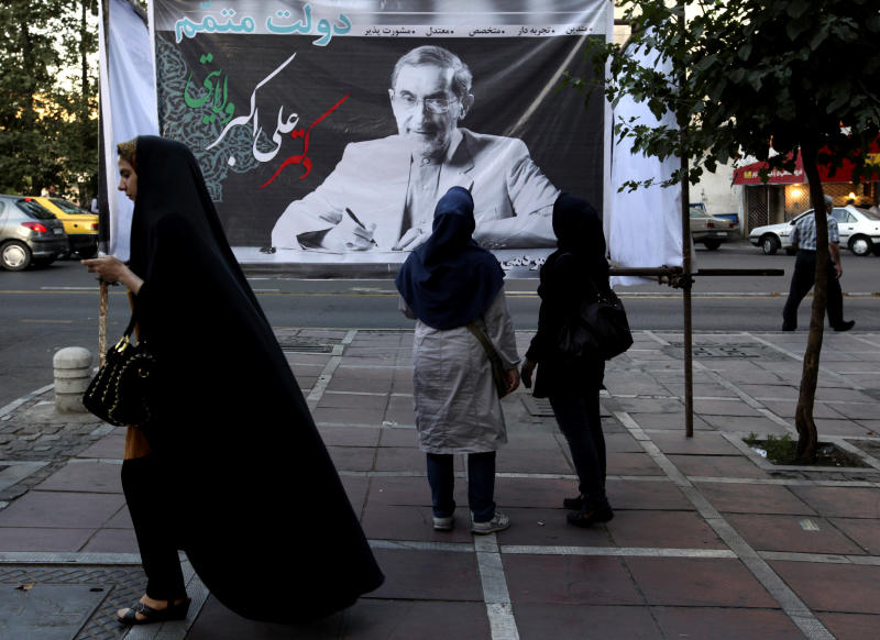 Two Iranian women look at a banner of presidential candidate Ali Akbar Velayati, a conservative Foreign Minister, a day prior to the election, in Tehran, Iran, Thursday, June 13, 2013. Iran's presidential election on Friday may be defined by who doesn't vote. Liberal-leaning Iranians debated whether to stay away in silent protest or support the lone relatively moderate candidate and indirectly endorse what they claim is an undemocratic system. (AP Photo/Vahid Salemi)