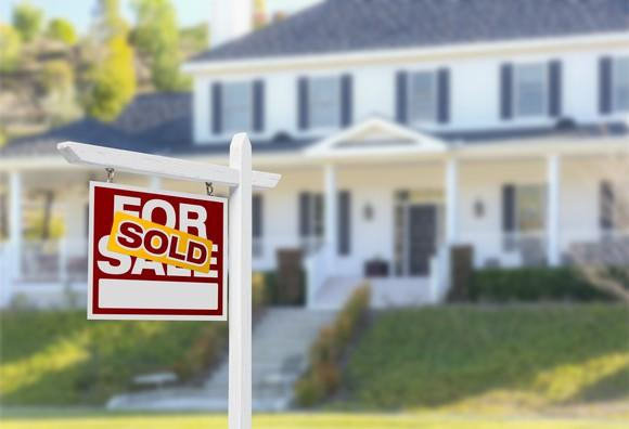 For sale sign outside of home, with a sold sticker