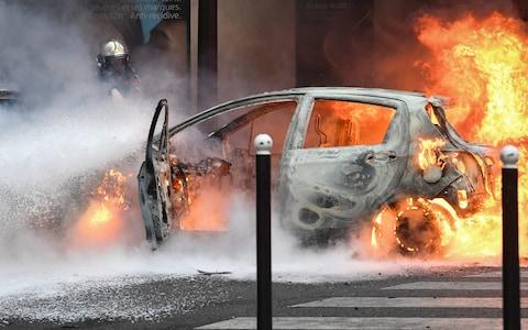 A firefighter stands next to a car set on fire during a protest of Yellow vest - Credit: ALAIN JOCARD/AFP/Getty Images