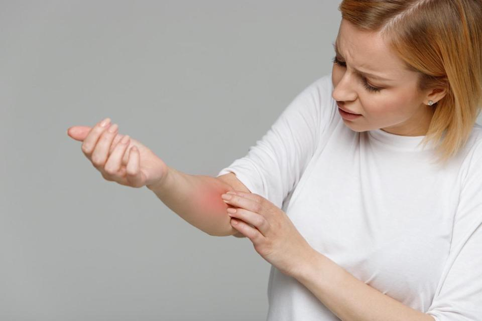 Woman removing adhesive plaster from the wound after blood test injection