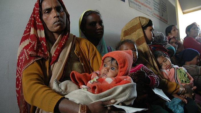 Archive image showing Indian women waiting in line with children for vaccine clinic