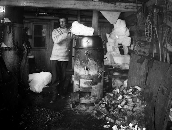 """The Belgica's second engineer, Max van Rysselberghe, melts snow on the Belgica's stove.<span class=""""copyright"""">De Gerlache Family Collection</span>"""