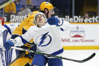 Tampa Bay Lightning center Yanni Gourde, front, falls to the ice after calling with Nashville Predators center Ryan Johansen (92) in the second period of an NHL hockey game Saturday, April 10, 2021, in Nashville, Tenn. (AP Photo/Mark Humphrey)