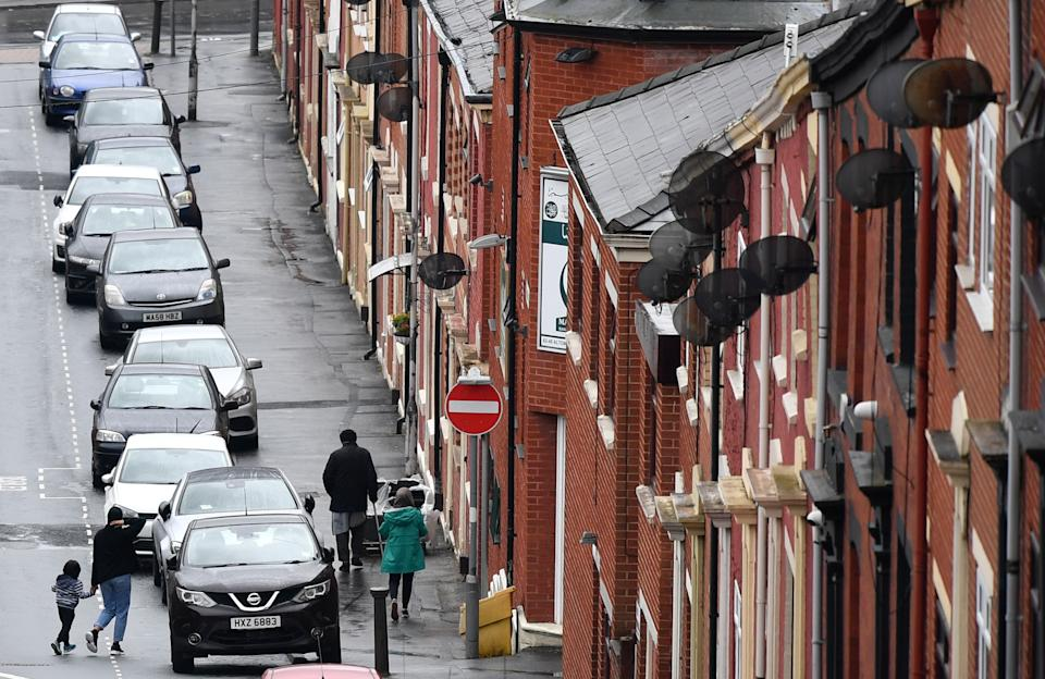 Pedestrians walk past rows of terraced houses in a residential street in Blackburn, north west England, on July 15, 2020, following news that there has been a spike in the number novel coronavirus COVID-19 cases in the area. (Photo by Paul ELLIS / AFP) (Photo by PAUL ELLIS/AFP via Getty Images)