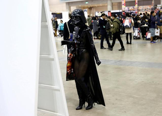 A woman in a Darth Vader costume reads a notice at Tokyo Comic Con at Makuhari Messe in Chiba, Japan December 1, 2017. REUTERS/Kim Kyung-Hoon