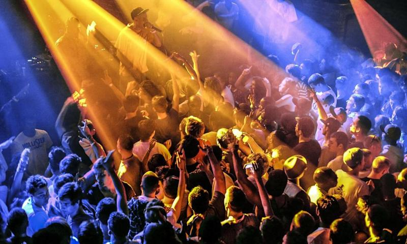 A packed dancefloor in a nightclub illuminated by blue and orange lights