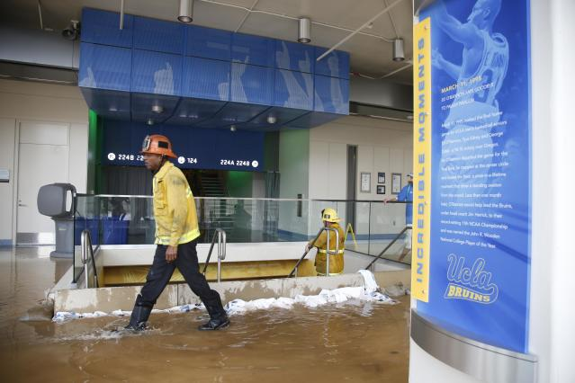 A firefighter walks past a dammed up stairway inside UCLA's Pauley Pavilion sporting arena as water flows from a broken thirty inch water main that was gushing water onto Sunset Boulevard near the UCLA campus in the Westwood section of Los Angeles July 29, 2014. The geyser from the 100-year old water main flooded parts of the campus and stranded motorists on surrounding streets. REUTERS/Danny Moloshok (UNITED STATES - Tags: DISASTER ENVIRONMENT)