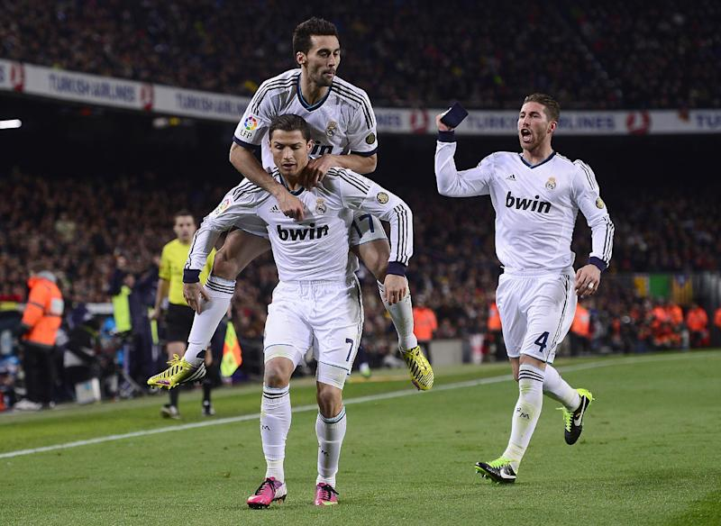Real's Cristiano Ronaldo from Portugal, from left, Alvaro Arbeloa and Sergio Ramos celebrate after scoring during a Copa del Rey soccer match between FC Barcelona and Real Madrid at the Camp Nou stadium in Barcelona, Spain, Tuesday, Feb. 26, 2013. (AP Photo/Manu Fernandez)