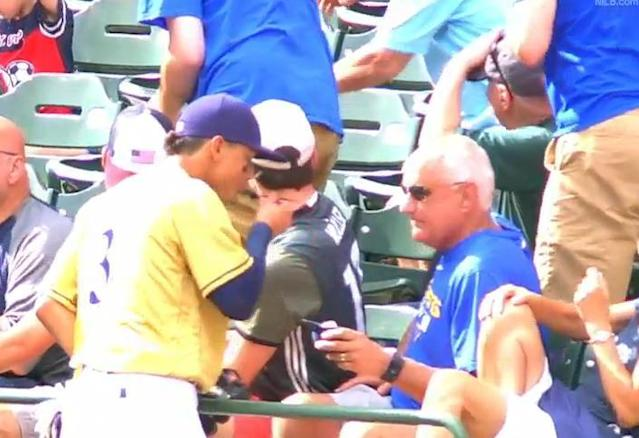Brewers shortstop Orlando Arcia steals a bite of ice cream from an unsuspecting fan during Saturday's game at Miller Park. (MLB)