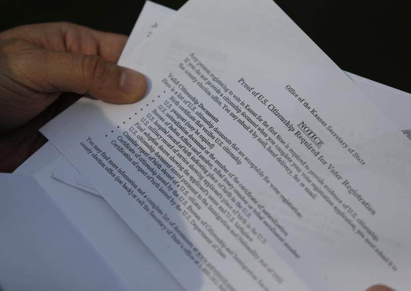 Aaron Belenky shows part of a letter from election officials while standing in front of his apartment in Overland Park, Kan., Wednesday, Aug. 14, 2013. The letter lists the valid citizenship documents needed to register to vote in Kansas for the first time. Belenky allowed the American Civil Liberties Union to list him as one of three aggrieved voters in a notice sent this week to Kansas Secretary of State Kris Kobach. (AP Photo/Orlin Wagner)
