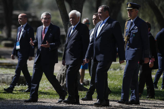 Head of the Hellenic Olympic committee Spyros Kapralos, second right, Greek President Prokopis Pavlopoulos, second left, and IOC President Thomas Bach, left, arrive to the flame lighting ceremony at the closed Ancient Olympia site, birthplace of the ancient Olympics in southern Greece, Wednesday, March 11, 2020. Greek Olympic officials are holding a pared-down flame-lighting ceremony for the Tokyo Games due to concerns over the spread of the coronavirus. Both Wednesday's dress rehearsal and Thursday's lighting ceremony will be closed to the public, while organizers have slashed the number of officials from the International Olympic Committee and the Tokyo Organizing Committee, as well as journalists at the flame-lighting. (AP Photo/Thanassis Stavrakis)