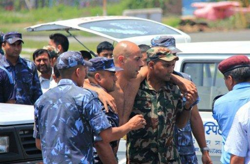 A survivor of a plane crash in northern Nepal is assisted off an aircraft after being evacuated for medical attention to Pokhara Airport. The small plane crashed near a treacherous high-altitude airport, killing 15 people while six others survived