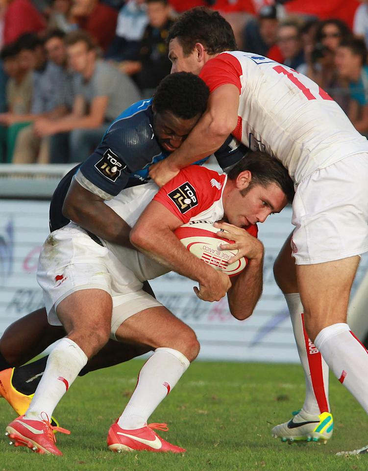 Biarrritz's Dimitri Yachvili, center, is tackled by Montpellier's Fulgence Ouedraogo during their French Top 14 rugby union match at the Stade Aguilera, in Biarritz, southwestern France, Saturday Aug. 24, 2013. (AP Photo/Bob Edme)