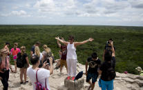 In this Aug. 1, 2018 photo, a tourist holds her ams out for a picture atop a pyramid at the Mayan archeological site of Coba in Mexico's Yucatan Peninsula. Mexico's president-elect Andres Manuel Lopez Obrador wants to build a $3.2 billion train that would run from the Yucatan Peninsula's resort of Cancun, to the Mayan ruins of Palenque in Chiapas. (AP Photo/Eduardo Verdugo)