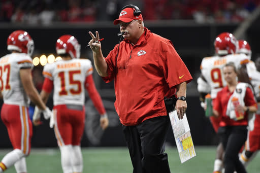 FILE - In this Aug. 17, 2018, file photo, Kansas City Chiefs head coach Andy Reid communicates with his team against the Atlanta Falcons during the first half of an NFL preseason football game in Atlanta. Halfway through the season, Reid is a candidate for coach of the year. (AP Photo/John Amis, File)