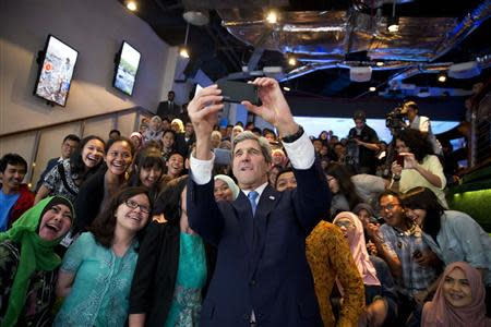 U.S. Secretary of State John Kerry takes a selfie with a group of students before delivering a speech on climate change in Jakarta