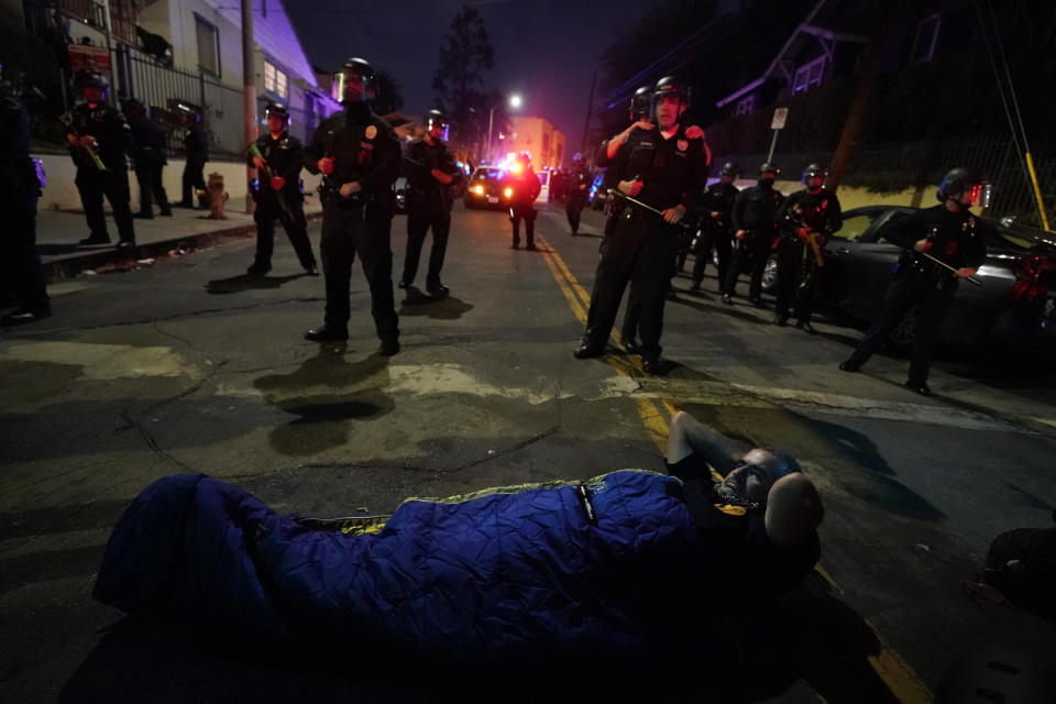 A demonstrator sets up a sleeping bag in front of police in the Echo Park section of Los Angeles Thursday, March 25, 2021. Demonstrators gathered Wednesday night to protest the planned temporary closure of a Los Angeles park that would displace a large homeless encampment, which has grown throughout the coronavirus pandemic. (AP Photo/Marcio Jose Sanchez)