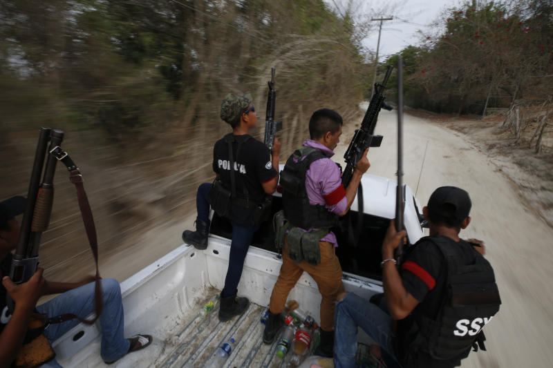 """FILE - In this May 29, 2019 file photo, members of a FUPCEG vigilante group patrol in Xaltianguis, Guerrero state, Mexico. President Andres Manuel Lopez Obrador said Thursday, Aug. 22, that he disagreed with his assistant interior secretary's decision to attend a ceremony with vigilantes, who often call themselves """"self-defense"""" groups. """"We cannot have illegal groups performing law enforcement duties. That cannot be allowed,"""" Lopez Obrador said. (AP Photo/Rebecca Blackwell, File)"""