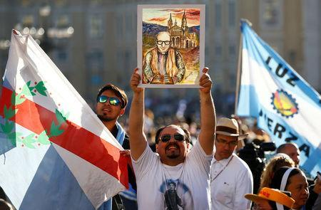A faithful holds a painting of Giuseppe Gabriele Del Rosario Brochero, one of the new seven saints, before the start of a canonization mass led by Pope Francis in Saint Peter's Square at the Vatican October 16, 2016. REUTERS/Tony Gentile